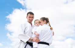 Portrait of young sports family in a kimono against the background of the sky royalty free stock photos