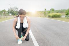 Portrait of young sports girl tying shoelaces on the road. Running athlete girl. Portrait of young sports girl tying shoelaces on the road. Healthy lifestyle Stock Photos