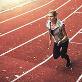 Portrait of young sportswoman running fast on track field Stock Image