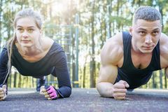 Portrait of young sporty couple doing the plank exercise outdoors royalty free stock photo