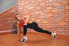 Portrait of young sporty girl doing stretching exercise Royalty Free Stock Photography