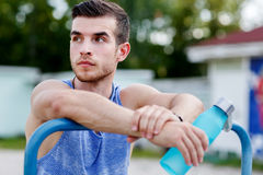 Portrait of young sporty men holding blue water bottle Royalty Free Stock Photos