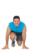 Portrait of a young sporty smiling man in running stance Stock Images