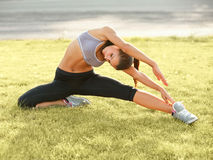 Portrait of Young Sporty Woman Doing Stretching Exercise. Royalty Free Stock Photos