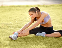 Portrait of Young Sporty Woman Doing Stretching Exercise. Stock Photo