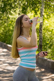 Portrait of young sporty woman drinking isotonic drink at street. Portrait of young sporty woman drinking isotonic drink at park. Woman in a  striped shirt in Stock Images