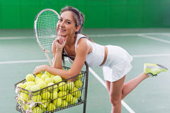 Portrait of a young sporty woman posing on tennis court. Royalty Free Stock Photos