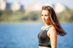 Portrait of young sporty woman resting after jog. Ging in park near lake. Portrait of athletic girl in black top after fitness workout. Healthy lifestyle image Royalty Free Stock Image