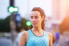 Portrait of young sporty woman resting after jog. Ging in the evening city. Portrait of athletic girl in blue top at sunset Royalty Free Stock Photography