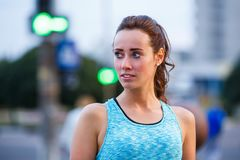 Portrait of young sporty woman resting after jog. Ging in the evening city. Portrait of athletic girl in blue top at sunset Stock Images