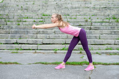 Portrait of young sporty woman in sport dress does stretching exercises outdoor.  Royalty Free Stock Photo
