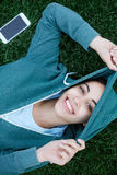 Portrait of young and sporty woman in sportswear lies with the smartphone on the grass in park Royalty Free Stock Images