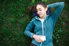 Portrait of young and sporty woman in sportswear Lies with the smartphone on the grass in park Stock Photography