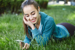 Portrait of young and sporty woman in sportswear Lies with the smartphone on the grass in park Stock Image