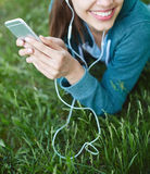 Portrait of young and sporty woman in sportswear Lies with the smartphone on the grass in park Royalty Free Stock Photography