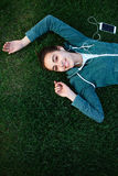 Portrait of young and sporty woman in sportswear Lies with the smartphone on the grass in park Stock Photo