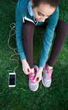 Portrait of young and sporty woman in sportswear sits with the smartphone on the grass in park Royalty Free Stock Image