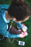 Portrait of young and sporty woman in sportswear sits with the smartphone on the grass in park Royalty Free Stock Photography