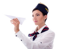 Portrait of young stewardess holding paper plane isolated on whi Royalty Free Stock Photos