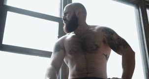 Portrait of young strong muscular Caucasian man resting after extreme power training at large gym window slow motion. Motivation and reaching goals, shirtless stock footage
