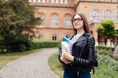 Portrait of young student female outdoors in university during break and holding books, education concept. Portrait of young student female outdoors in stock photography