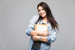 Portrait of young student holding a book over grey background stock image