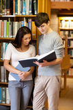 Portrait of young students reading a book. In the library Stock Images