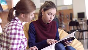 Portrait of young students in reading room looking for necessary information in books stock footage