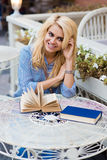 Portrait of a young stunning lady with cute smile sitting with books in sidewalk cafe during her recreation time,. Charming happy Caucasian woman enjoying her Stock Photography