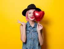 Girl with pink hair style with heart shape ballon. Portrait of young style hipster girl with pink hair style with heart shape balloon on yellow background. St Stock Photo