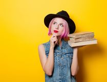 Hipster girl with pink hairstyle with books. Portrait of young style hipster girl with pink hairstyle with books on yellow background Royalty Free Stock Images