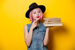 Hipster girl with pink hairstyle with books. Portrait of young style hipster girl with pink hairstyle with books on yellow background Stock Images