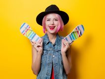 Girl with pink hairstyle and flip flops shoes. Portrait of young style hipster girl with pink hairstyle and flip flops shoes on yellow background Stock Images