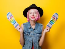 Girl with pink hairstyle and flip flops shoes. Portrait of young style hipster girl with pink hairstyle and flip flops shoes on yellow background Royalty Free Stock Images