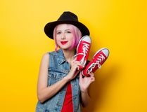 Girl with pink hairstyle and red gumshoes. Portrait of young style hipster girl with pink hairstyle and red gumshoes on yellow background Royalty Free Stock Images