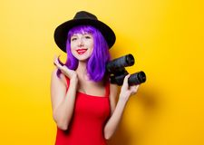 Hipster girl with purple hairstyle and binoculars. Portrait of young style hipster girl with purple hairstyle and binoculars on yellow background Royalty Free Stock Images