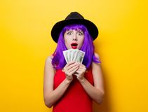 Hipster girl with purple hairstyle with money. Portrait of young style hipster girl with purple hairstyle with money on yellow background Royalty Free Stock Image