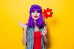 Hipster girl with purple hairstyle with pinwheel. Portrait of young style hipster girl with purple hairstyle with pinwheel on yellow background Royalty Free Stock Photography