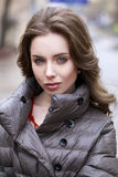 Portrait of a Young stylish brunette girl in a gray down jacket Stock Photo