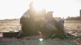 Portrait of young stylish family in casualwear sitting on plaid by waterside and having hot drinks at picnic. Cold. Weather, weekend recreation. Lens flares on stock video