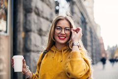 Young stylish girl student wearing bright yellow sweatshirt.Close-up portrait of inspired young woman laughing and touching glasse. Portrait young stylish girl Stock Photo