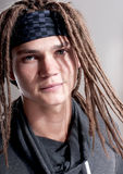 Portrait on young stylish guy with dreadlocks. Portrait on young stylish guy with dreadlocks on  gray background Royalty Free Stock Images