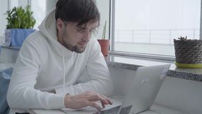 Portrait of a young stylish handsome bearded guy in a light sweatshirt and typing on a laptop while sitting at a table. Portrait young stylish handsome bearded stock video