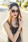 Portrait of a young stylish hipster girl dressed in dark cap and sunglasses royalty free stock image