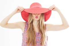 Portrait of young stylish kissing girl model in colour casual summer clothes in red pink hat with natural makeup and long blond. Hair isolated on stock photo