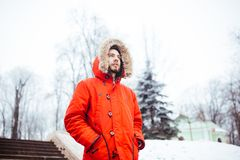 Portrait of a young stylish man with beard dressed in red winter jacket with hood and fur on his head stands against the backdrop. Of a snow-covered city and stock photo