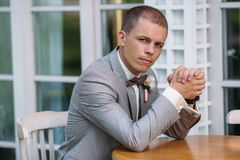 Portrait of a young stylish man in a classic business suit in gray with a white shirt and a bow tie. A young guy is a. Businessman is sitting at a table. The Royalty Free Stock Images