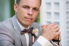 Portrait of a young stylish man in a classic business suit in gray with a white shirt and a bow tie. A young guy is a. Businessman is sitting at a table. The Stock Image