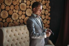 Portrait of a young stylish man in a classic business suit in gray with a white shirt and a bow tie. Young guy. Businessman puts on a watch on hand. The concept Royalty Free Stock Photo