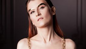 Portrait of a young stylish woman with gold metal eyebrows. Futurism, fashion of the future. Concept stock photography
